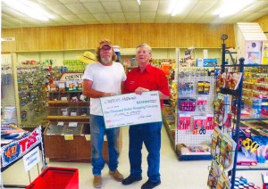 Mike Parker, Giveaway winner, accepts $1,000 check from Larry Carter of Carter's Hardway in Shirley.