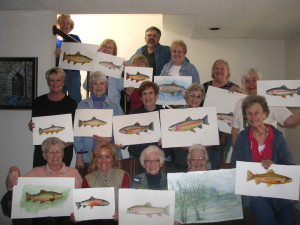 Artists show their watercolors featuring trout portraits or river scenes. Instructor Duane Hada stands in the back row at center. Artists are (back row, from left) Lea Berry, Julie Caswell, Alecs Long, Ellen Kelly, Jan Cobb, Joyce Hartmann; (middle row, left) Dianne Traylor, Carolyn Goettsch, Judy Shumann, Raylene Finkbeiner, Jeanne Homuth; (front row) Bonnie Hookman, Charlotte Rierson, Diana Foote, Ruby Krimm.                                                      Photo courtesy of Joyce Hartman