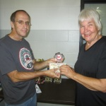 Tournament Director, Eugene Atha, presents Joyce Hartmann with a trophy and cash after the Arkansas Open Table Tennis Tournament at UALR, Little Rock.