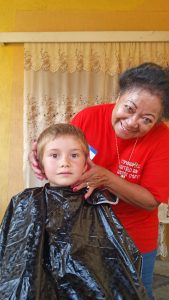 Mercie, one of the team members, cuts a childs hair prior to the start of school.